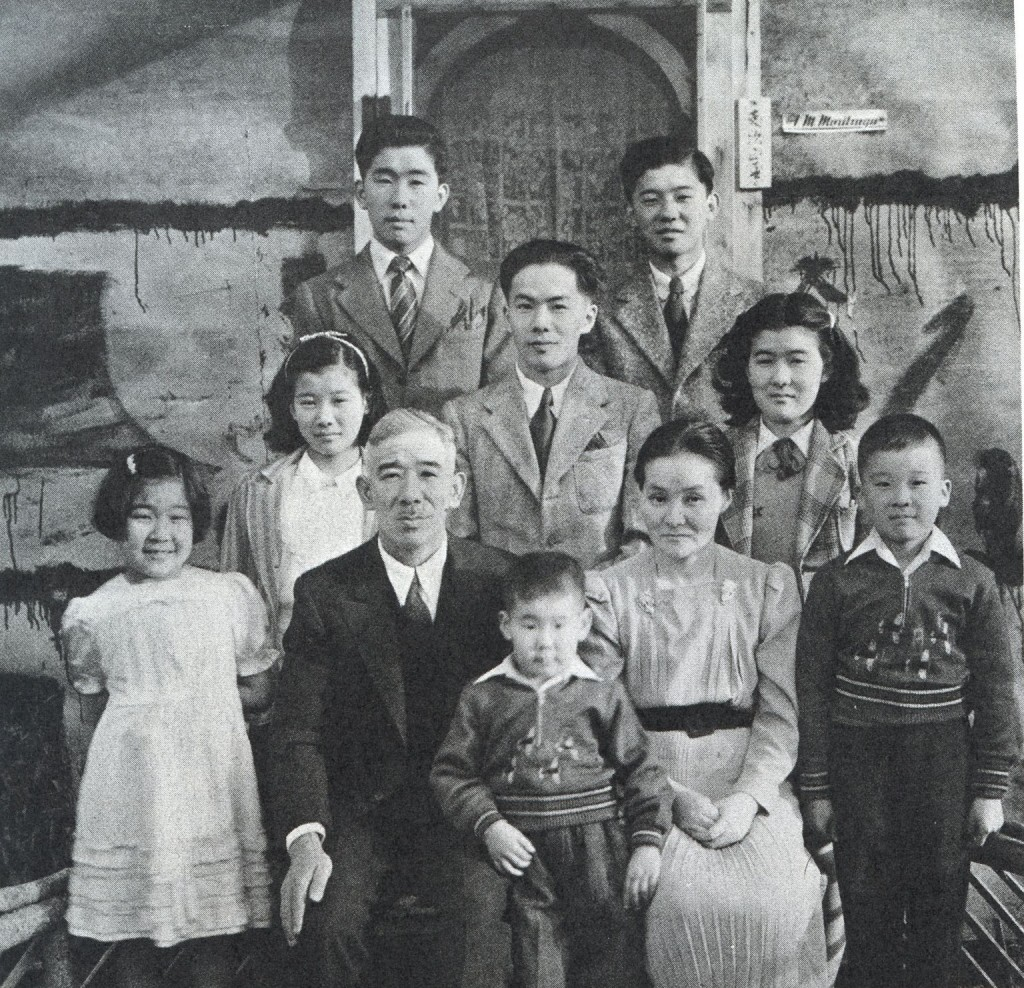 This photo shows the temporary reunion of the Moritsugu family with oldest sons Frank and Ken in February 1943. Taken outside their tarpaper shack at 620 Sixth Avenue are: Ken and Harvey at the rear; then June, Frank and Eileen; then Joyce, father Frank Masaharu Moritsugu, mother Shizuko, and Henry. Ted, the youngest, stands in front between his parents. Photo courtesy: Frank Moritsugu