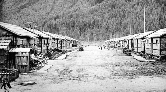 A black and white photo of a dirt road and shacks in Tashme. Photo courtesy: Nikkei Place