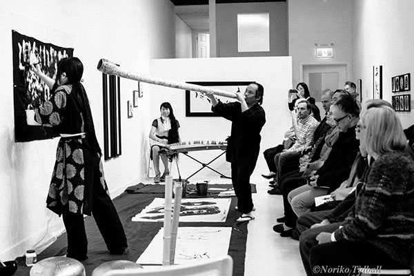 Etsuko Essence Inoue does calligraphy live in front of an audience, while Alcvin Ramos plays the shakuhachi. Photo courtesy Etsuko Essence Inoue.